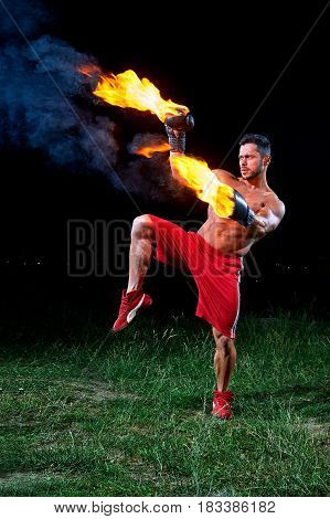 Vertical shot of a muscular aggressive fighter with burning boxing gloves training outdoors at night fire fiery flaming burn power strength sports fierce masculinity motivation effort energy.