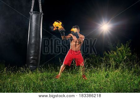 Shot of a powerful aggressive fighter with muscular strong body working out at night outdoors with his boxing gloves burning with fire copyspace sport power strength force effort activity sportsman.