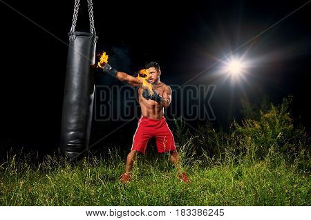 Shirtless muscular male boxer training outdoors at night exercising on a punching bag with his boxing gloves burning with fire copyspace fitness lifestyle forceful powerful confidence athlete.