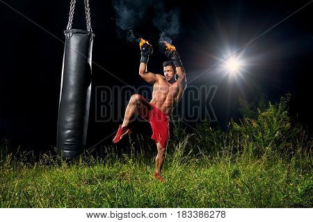 Full length shot of a handsome young muscular male fighter wearing boxing gloves burning with fire training on a punching bag outdoors at night copyspace athletics sports fitness martial arts combat.