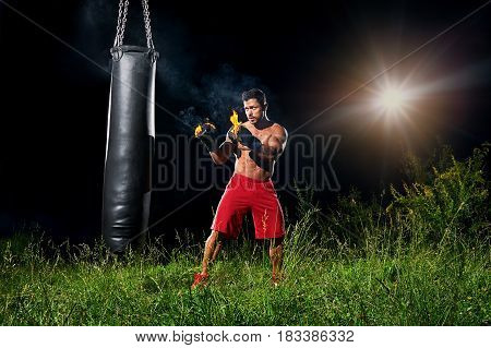 Powerful strong young muscular shirtless boxer with burning gloves training outdoors on a punching bag copyspace fire flames fiery force strength motivation sports sportsperson active athletics.
