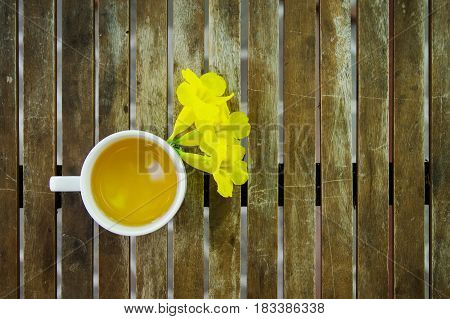 Cup of jasmine tea with yellow flowers on wooden table. Top view.