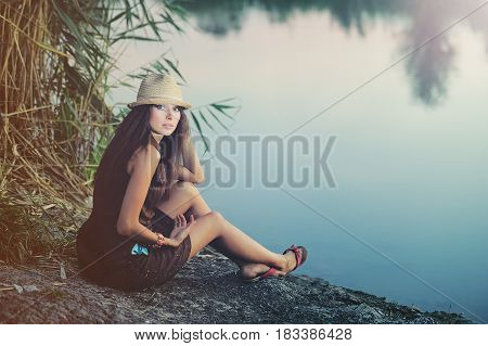Woman Resting On The Banks Of The River In The Evening