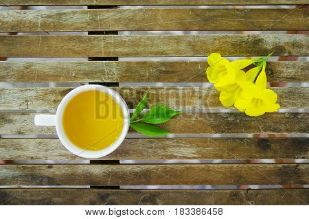 Cup of jasmine tea with green leaf & yellow flowers on wooden table. Top view.