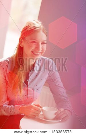 Smiling young businesswoman having coffee at table in office