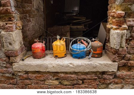Abandoned old rusty colorful gas cylinders (LPG or Liquefied petroleum gas) with tubes