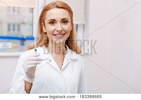 Precautionary measures. Attractive female keeping smile on her face holding syringe in right hand looking straight at camera