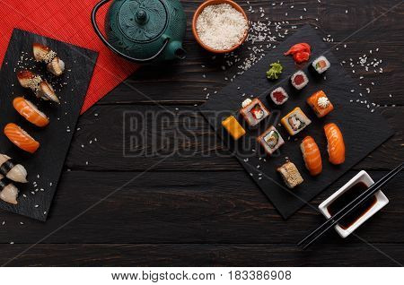 Sushi and rolls background, frame on black, top view. Colorful japanese restaurant food set with tea