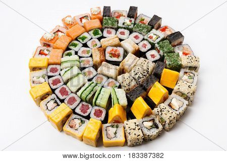 Sushi big party platter isolated on white background. Japanese food restaurant delivery - maki, unagi and california rolls set placed in circle