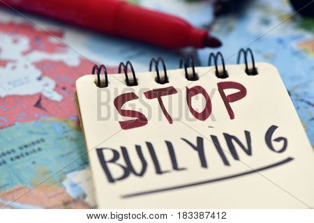 the text stop bullying written in a page of a spiral notebook and some marker pens on a blurred world map