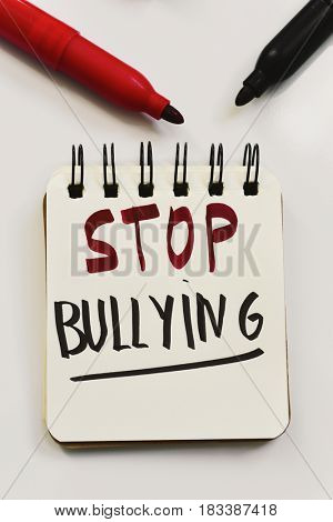 the text stop bullying written in a page of a spiral notebook and some marker pens on an off-white surface