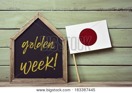 a house-shaped blackboard with the text golden week written in it and a flag of japan, against a pale green rustic wooden background