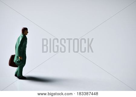 miniature traveler man carrying a suitcase on an off-white background with a blank space on the right
