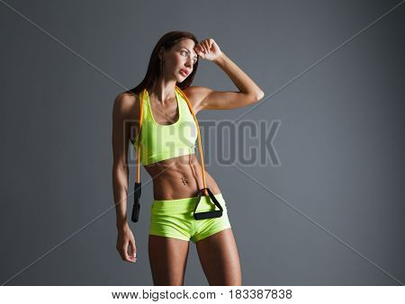 Beautiful healthy fitness woman exercising on gray background. Studio shoot.