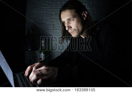 Picture of young concentrated man using laptop computer at home indoors at night. Looking aside.