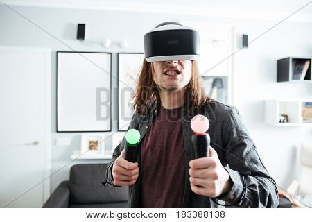 Image of young concentrated man sitting at home indoors play games with 3d virtual reality glasses.