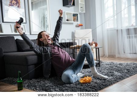 Photo of young cheerful man sitting at home indoors play games with joystick near crisps. Looking aside.