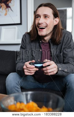 Image of young smiling man gamer sitting at home indoors and play games with joystick. Looking aside.