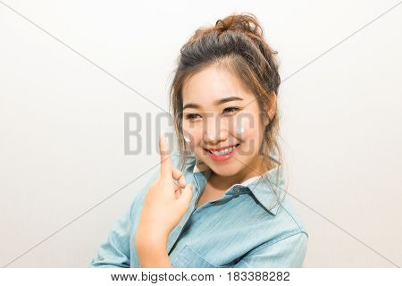 Young Asian Woman Smiling And Applying Moisturizing Cream On Her Face