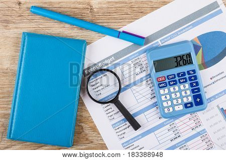 Printout Of Event Budget, Calculator, Notepad, Pen And Magnifying Glass