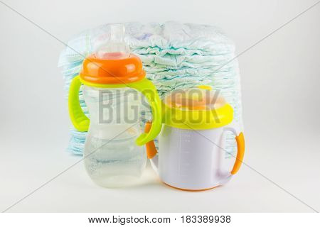 Baby diapers and bottles on a white background