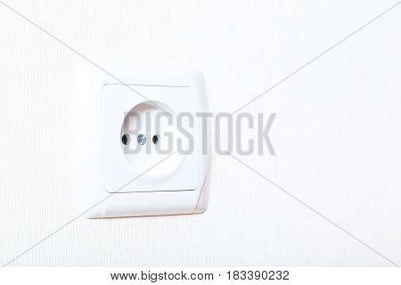 Electrical socket on a white wall, close up