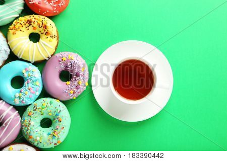 Tasty Donuts With Sprinkles With Cup Of Tea On Green Background