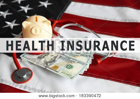 Text HEALTH INSURANCE with money and stethoscope on USA flag background