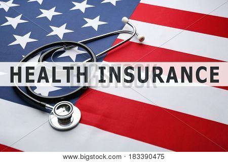 Text HEALTH INSURANCE and stethoscope on USA flag background