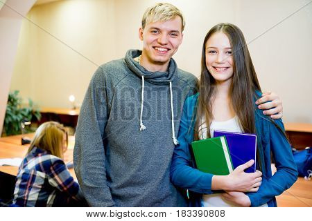 Portrait of two smiling college students on campus