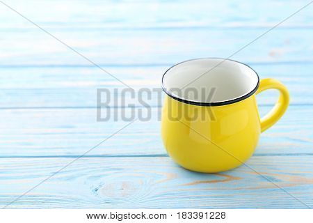 Yellow mug on blue wooden table, close up