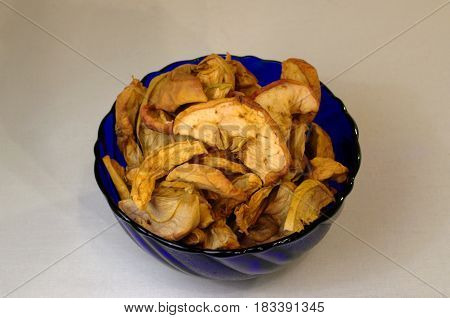Dried apple chips in a blue glass cup