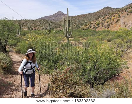 CAVE CREEK, ARIZONA, APRIL 16. Spur Cross Ranch Conservation Area on April 16, 2017, near Cave Creek, Arizona. A Smiling Woman Hikes in Spur Cross Ranch Conservation Area in Arizona.