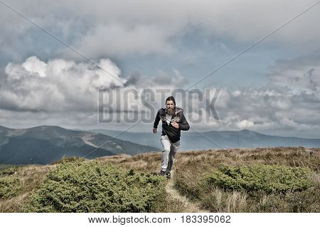man runs on the green meadow in mountain on cloudy sky background bearded guy runner workout outdoor sport and recreation business and success