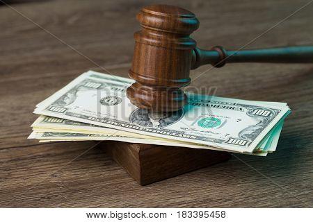 Photo of hammer on dollars
