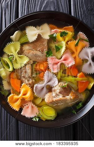 Hearty Meat Soup, With Colored Farfalle Pasta And Vegetables Close-up. Vertical Top View