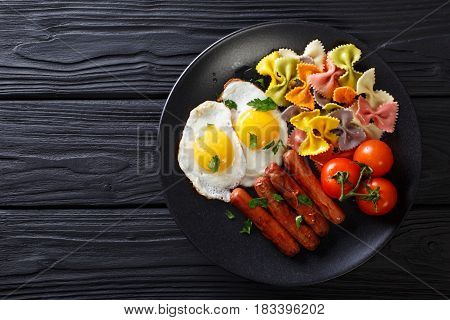 Hearty Breakfast: Fried Eggs, Sausages, Farfalle Pasta And Tomatoes Close-up. Horizontal Top View