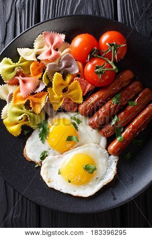 Fried Egg, Sausages, Pasta Farfalle And Tomato Close-up. Vertical Top View