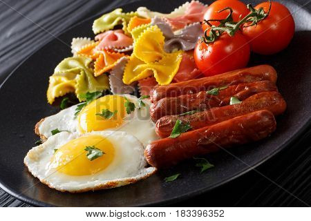 Fried Egg, Sausages, Pasta Farfalle And Tomato Close-up. Horizontal