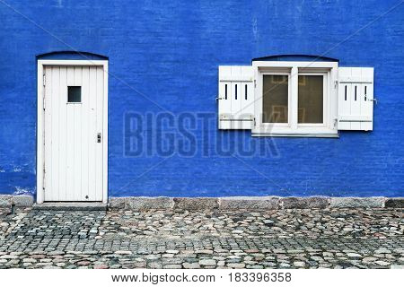 Blue wall with white door and window with opened shutters, facade of the old brick house
