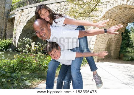Father Makes A Piggyback With His Son And His Beautiful Girl