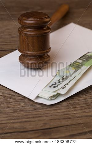 Wooden table with hammer, banknotes