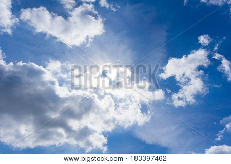 Clouds and Sun in Spring. Cloudy Day. White Clouds on a blue Sky