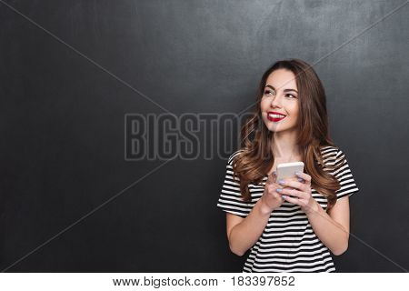 Smiling young woman thinking while using smartphone