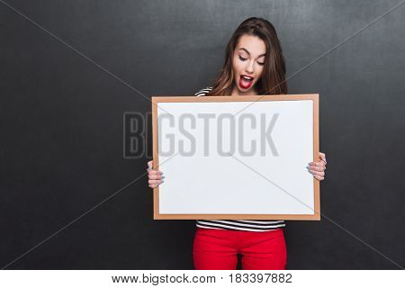 Young positive woman wearing casual surprising and holding blank placard over head isolated