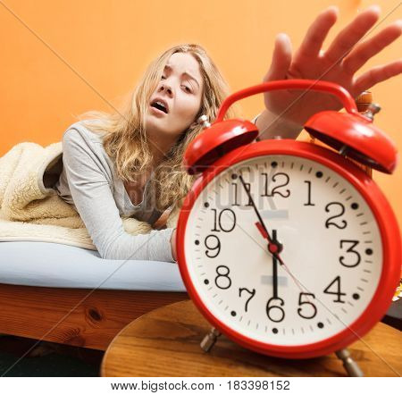 Exhausted woman waking up in bed turning off alarm clock. Young girl in the morning.
