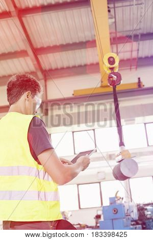 Mature manual worker with digital tablet operating crane to lift steel in industry