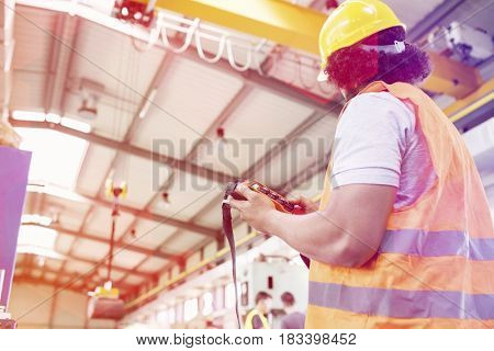 Low angle view of young manual worker operating crane in factory
