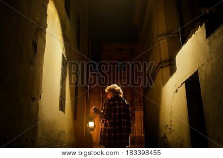 Mysterious Blonde Woman In Elegant Retro Coat With Old Oil Lantern Walking In Old French Street In P