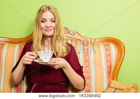 Fashionable woman drinking cup of coffee sitting on vintage sofa. Young girl with hot energizing beverage stay awake. Caffeine energy.